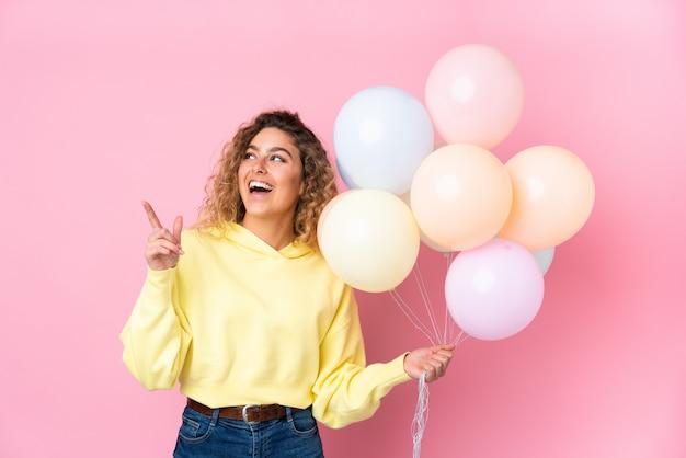 Giovane donna bionda con capelli ricci che prende molti palloni isolati sulla parete rosa che indica con il dito indice una grande idea