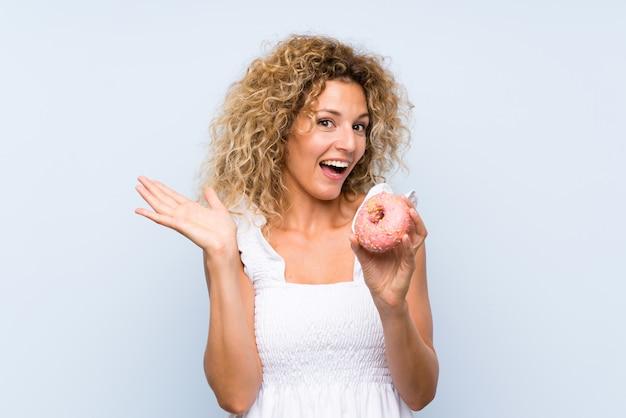 Giovane donna bionda con capelli ricci che tengono una ciambella sopra la parete blu isolata con espressione facciale colpita