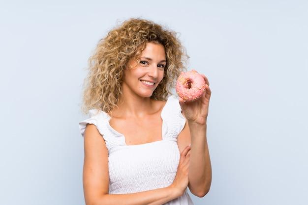 Giovane donna bionda con capelli ricci che tiene una ciambella sopra la parete blu che osserva in su mentre sorridendo