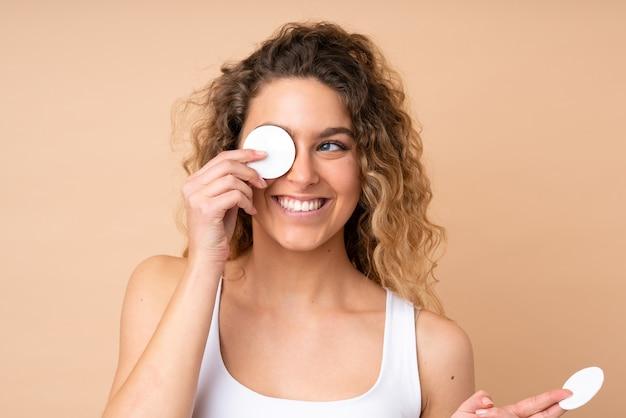 Giovane donna bionda con capelli ricci isolato su beige con un batuffolo di cotone per rimuovere il trucco dal viso e sorridente