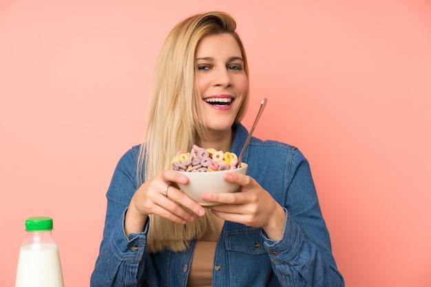 Giovane donna bionda con ciotola di cereali
