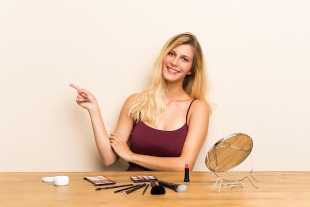 Giovane donna bionda con cosmetici in una tabella che punta il dito verso il lato