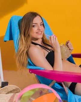 Giovane donna bionda con drink rinfrescante sulla spiaggia