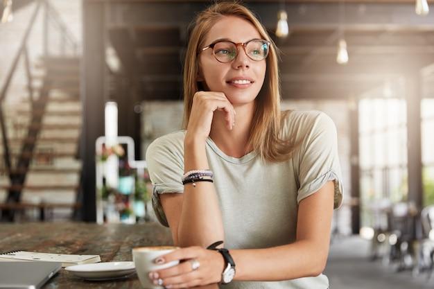 Giovane donna bionda con gli occhiali nella caffetteria