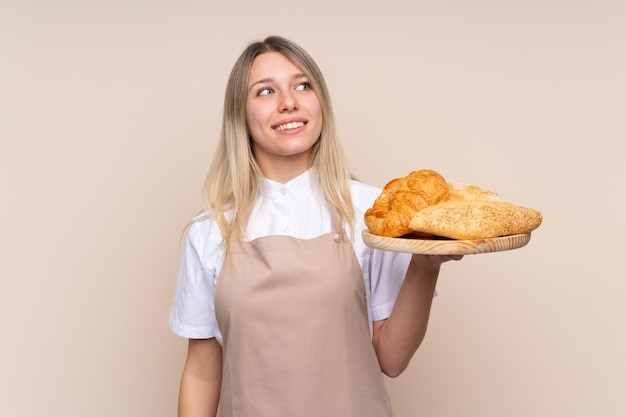 Giovane donna bionda con grembiule. panettiere femminile che tiene una tabella con parecchi pani che osservano in su mentre sorridendo