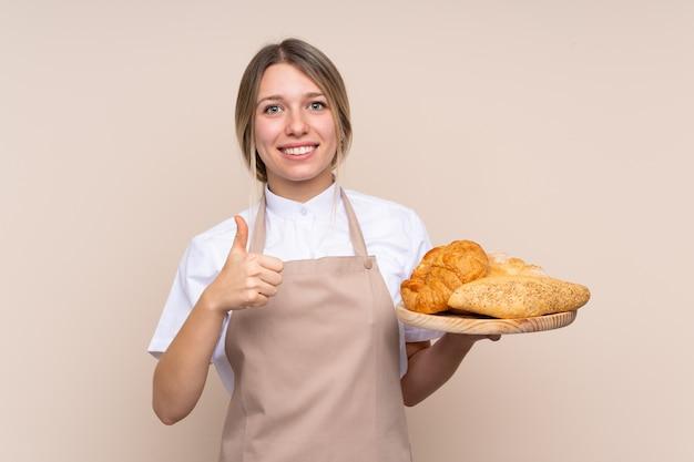 Giovane donna bionda con grembiule. panettiere femminile in possesso di un tavolo con diversi pani con il pollice in alto perché è successo qualcosa di buono