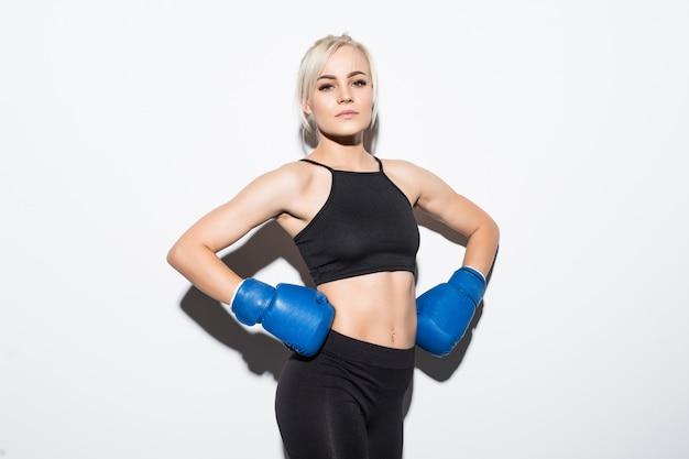 Giovane donna bionda con guantoni da boxe blu pronti a vincere su bianco