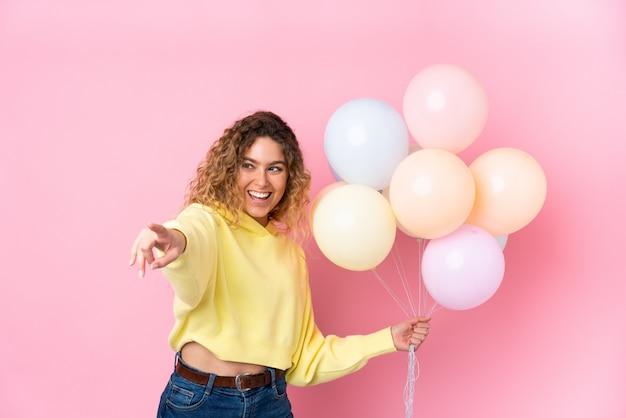 Giovane donna bionda con i capelli ricci che cattura molti palloncini sul dito puntato rosa al lato