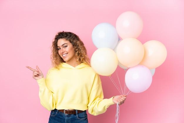 Giovane donna bionda con i capelli ricci che cattura molti palloncini sul muro rosa che punta il dito verso il lato