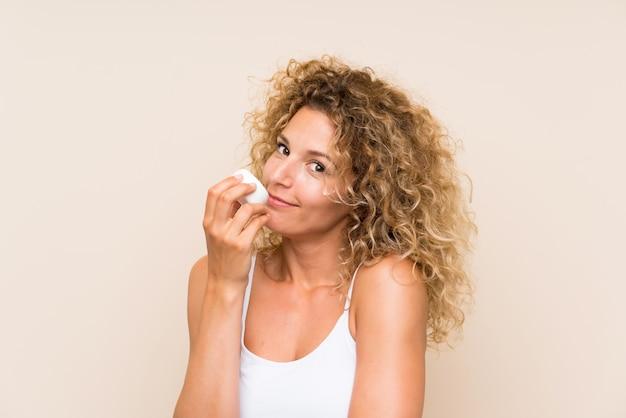 Giovane donna bionda con i capelli ricci con crema idratante