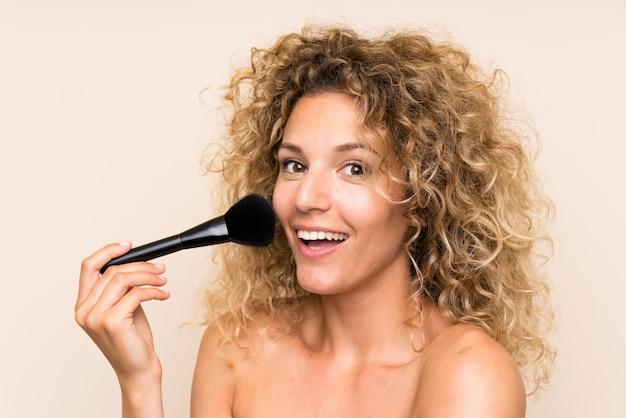 Giovane donna bionda con i capelli ricci con pennello trucco