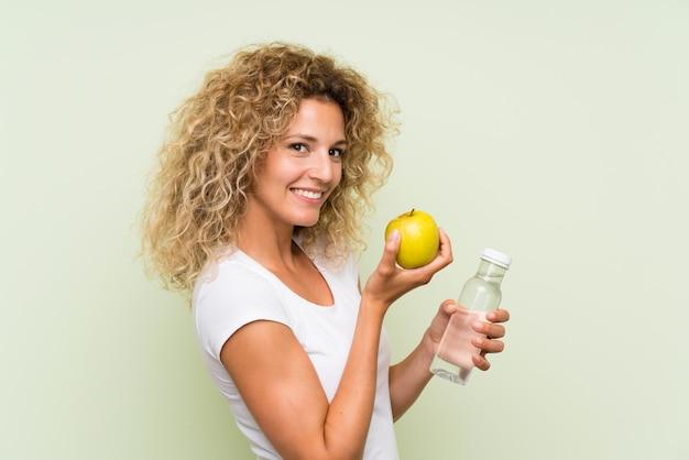Giovane donna bionda con i capelli ricci con una mela e con una bottiglia di acqua