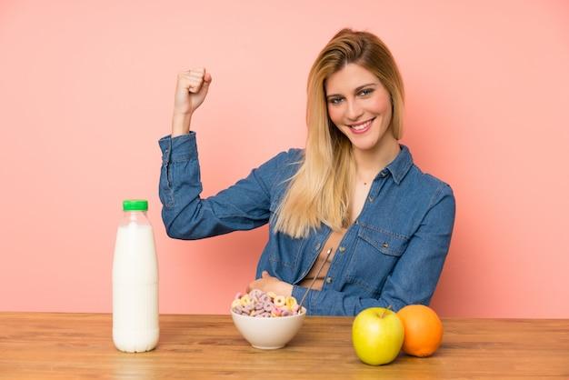 Giovane donna bionda con la ciotola di cereali che fa forte gesto