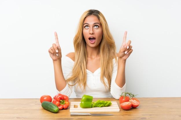 Giovane donna bionda con le verdure in una tabella che indica con il dito indice
