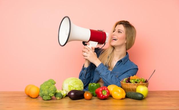 Giovane donna bionda con molte verdure che gridano attraverso un megafono