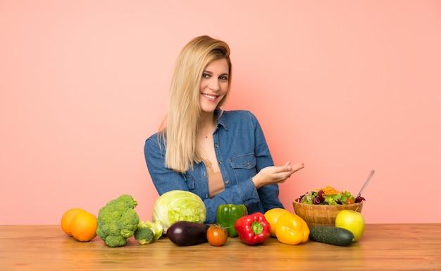 Giovane donna bionda con molte verdure che presentano un'idea mentre guardando sorridere verso