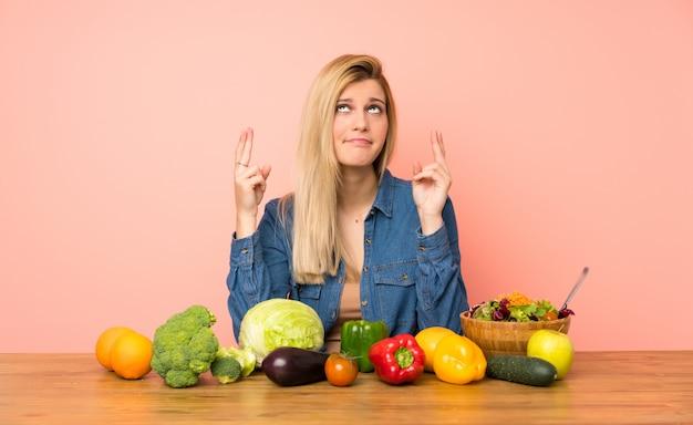 Giovane donna bionda con molte verdure con le dita che attraversano e che desiderano il meglio