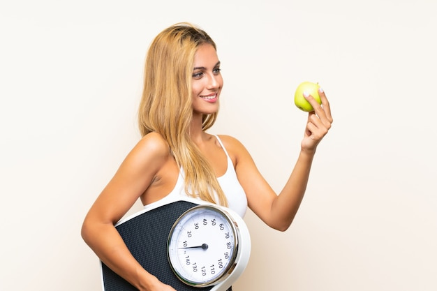 Giovane donna bionda con pesatrice e con una mela