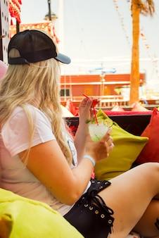 Giovane donna bionda con un bicchiere di coctail nella caffetteria