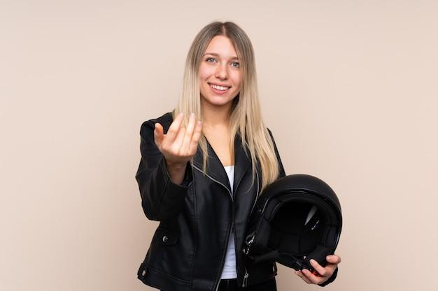 Giovane donna bionda con un casco da motociclista che invita a venire