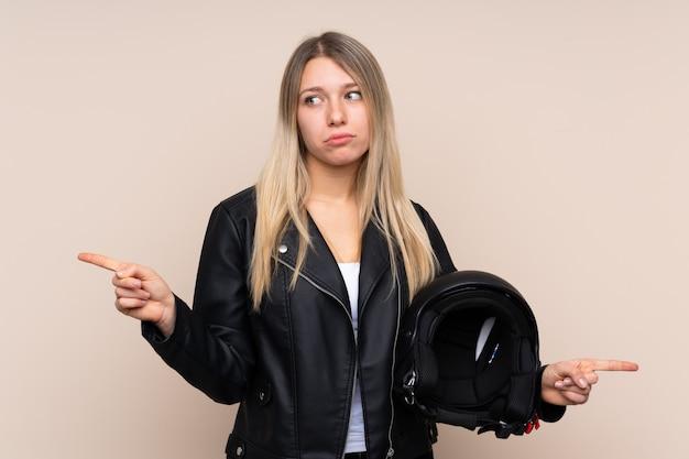 Giovane donna bionda con un casco da motociclista che punta ai laterali avendo dubbi