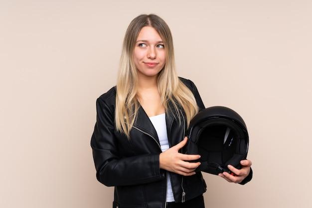 Giovane donna bionda con un casco da motociclista in piedi e guardando al lato