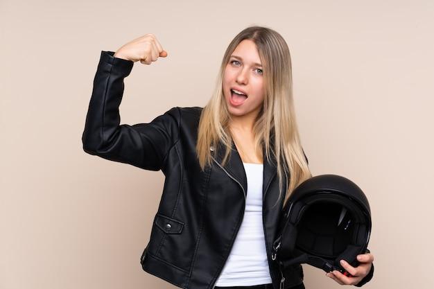 Giovane donna bionda con un casco del motociclo sopra la parete isolata che fa forte gesto