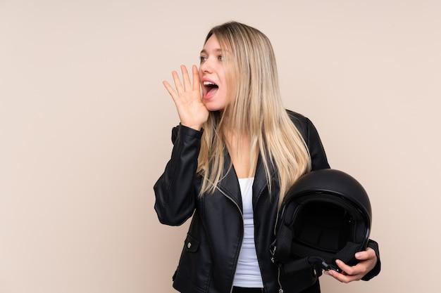 Giovane donna bionda con un casco del motociclo sopra la parete isolata che grida con la bocca spalancata