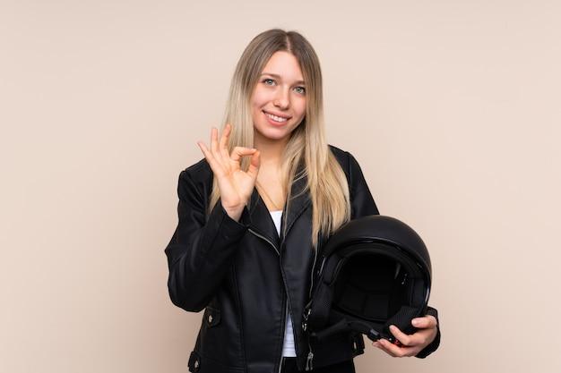 Giovane donna bionda con un casco del motociclo sopra la parete isolata che mostra un segno giusto con le dita