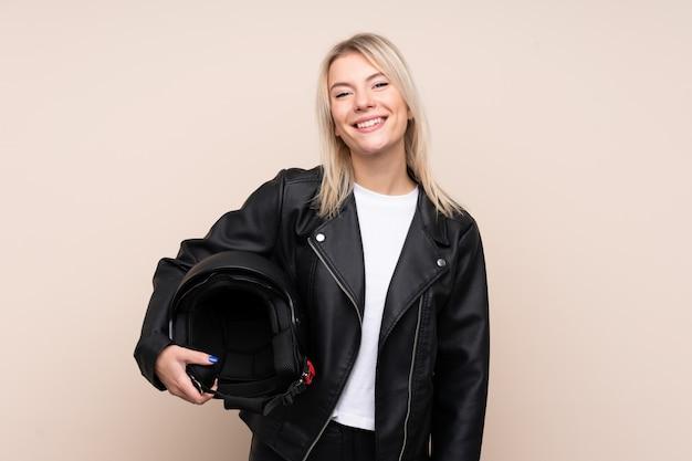Giovane donna bionda con un casco del motociclo sopra la parete isolata che sorride molto