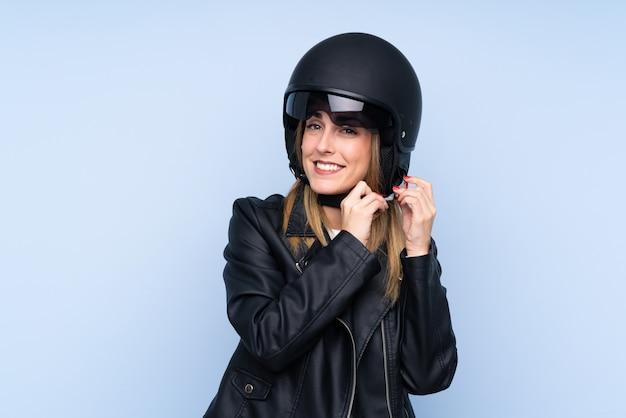 Giovane donna bionda con un casco del motociclo sopra la parete isolata
