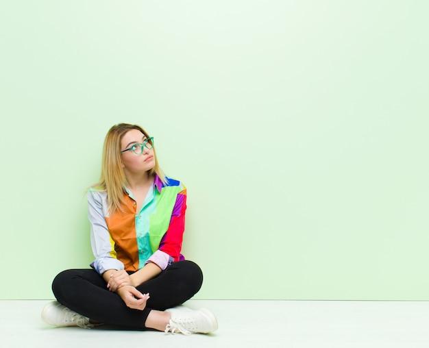 Giovane donna bionda con un'espressione preoccupata, confusa, all'oscuro, alzando lo sguardo per copiare lo spazio, dubitando seduta sul pavimento