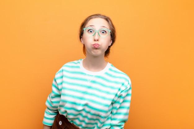 Giovane donna bionda con un'espressione sciocca, pazza, sorpresa, guance gonfie, sentirsi imbottita, grassa e piena di cibo