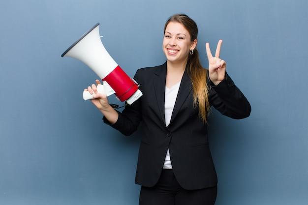 Giovane donna bionda con un megafono contro la parete del grunge