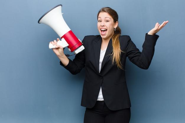 Giovane donna bionda con un megafono sulla parete del grunge
