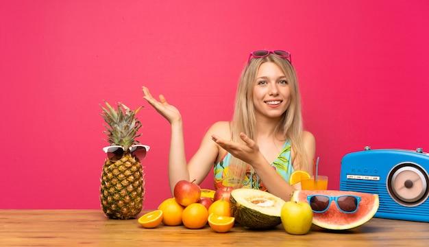 Giovane donna bionda con un sacco di frutta che estende le mani al lato