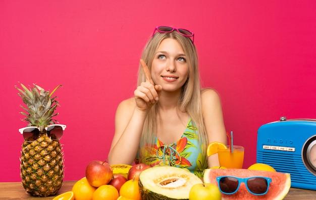Giovane donna bionda con un sacco di frutta che tocca sullo schermo trasparente