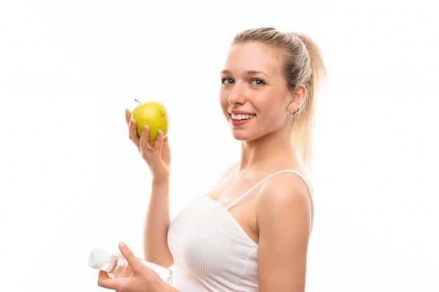 Giovane donna bionda con una mela e una bottiglia di acqua