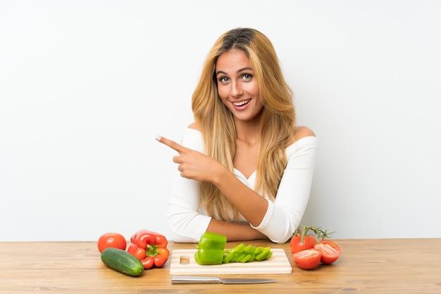 Giovane donna bionda con verdure in un tavolo che punta il dito verso il lato