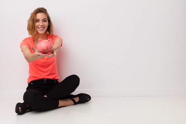 Giovane donna bionda contro la parete di colore piatto con un salvadanaio