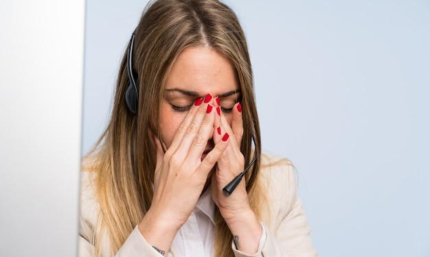 Giovane donna bionda del telemarketer sopra la parete blu isolata e sollecitata