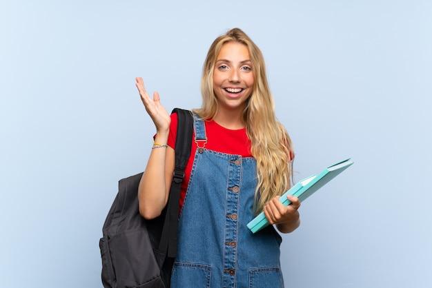 Giovane donna bionda dello studente sopra la parete blu isolata con espressione facciale di sorpresa