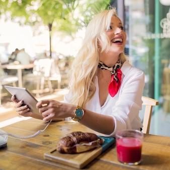 Giovane donna bionda di risata che attacca cavo sulla compressa digitale nel cafã