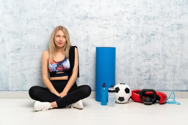 Giovane donna bionda di sport che si siede sul pavimento che sta e che guarda al lato