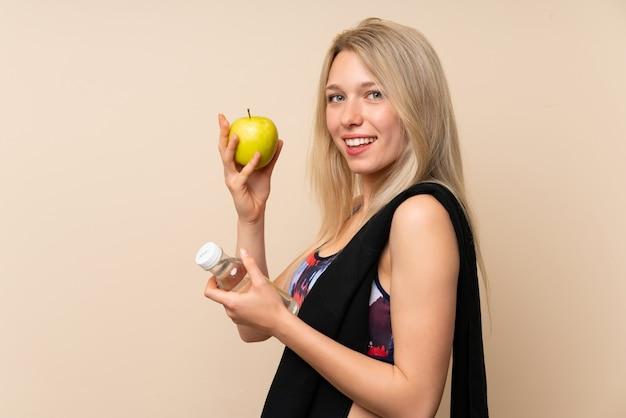 Giovane donna bionda di sport con una mela e una bottiglia di acqua