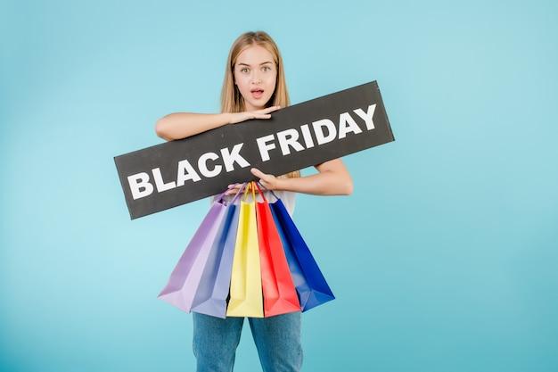 Giovane donna bionda emozionante con il segno di venerdì nero e sacchetti della spesa variopinti isolati sopra il blu