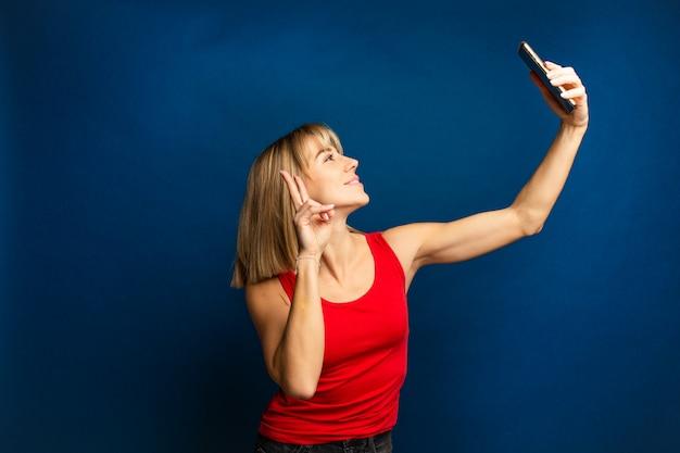 Giovane donna bionda esile che porta una camicia rossa che prende un selfie
