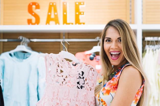 Giovane donna bionda felice che mostra vestito in negozio