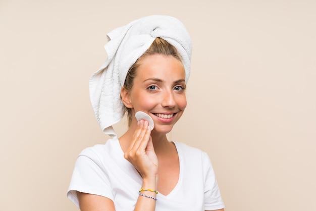 Giovane donna bionda felice che rimuove trucco dal suo fronte con il cuscinetto di cotone