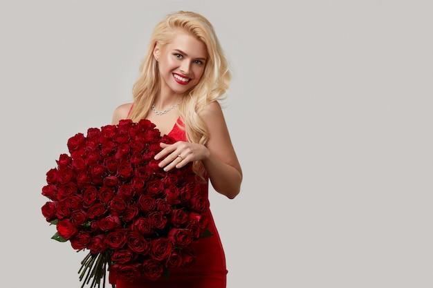 Giovane donna bionda felice che tiene un grande mazzo di rose rosse come regalo per l'8 marzo o il biglietto di s. valentino. indica l'anello di fidanzamento al dito.